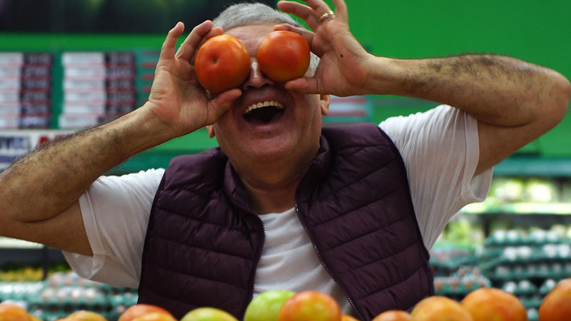 Man playing with tomatoes