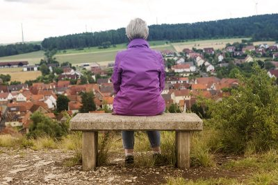 woman On Bench Overlooking Village